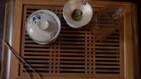Zamyka w górę ręk bierze zielonej herbaty filiżankę od drewnianego stołowego odgórnego widoku herbaciany kochanek zdjęcie wideo