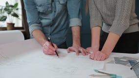 Zamyka w górę ręk dwa pracownika dyskutuje budynków rysunki w biurze Zbliżenie strzelanina ręka poruszający obrazki, dopatrywanie zbiory wideo