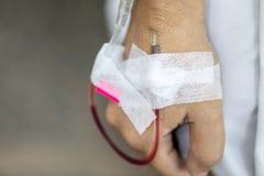Zamyka w górę ręki kobiety pacjenta z wtryskowy Zasolonym w ręce i podczas łgarskich rehabilitacj łóżek szpital fotografia royalty free