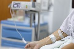 Zamyka w górę ręki kobiety pacjenta z wtryskowy Zasolonym w ręce i podczas łgarskich rehabilitacj łóżek szpital obraz stock