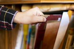 Zamyka w górę ręki rewizji i bierze czerwonego album fotograficznego na książkowej półce g obrazy stock