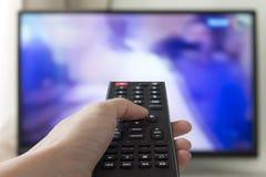 Zamyka w górę ręki trzyma TV pilot do tv z telewizją w tle obrazy stock