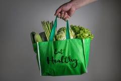 Zamyka w górę ręki trzyma zielonego sklepu spożywczego torbę z Je Zdrowego tekst Obrazy Royalty Free