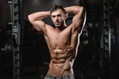 Zamyka w górę silnego abs faceta pokazuje w gym mięśniach obrazy royalty free