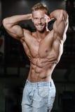 Zamyka w górę silnego abs faceta pokazuje w gym mięśniach Zdjęcia Royalty Free