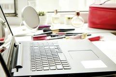 Zamyka w górę składu kobiety ` s stołowy wierzchołek z notebookiem i różnymi kosmetycznymi piękno akcesoriami Zdjęcia Royalty Free