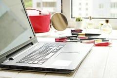 Zamyka w górę składu kobiety ` s stołowy wierzchołek z notebookiem i różnymi kosmetycznymi piękno akcesoriami Obrazy Royalty Free