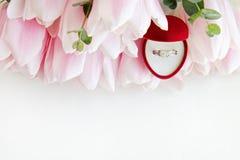Zamyka w górę składu z luksusowym diamentowym pierścionkiem i pięknym bukietem różowi tulipany zdjęcia royalty free