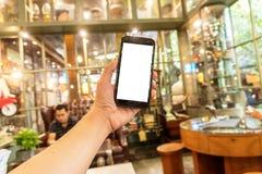 Zamyka w górę smartphone w sklep z kawą obrazy royalty free