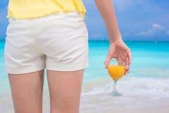 Zamyka w górę soku pomarańczowego w żeńskiej ręce na tle morze Obrazy Stock