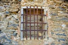 zamyka w górę starego drewnianego okno z barami blokuje dostęp w ścianie beton i kamień w zaniechanym domu żelazo, obrazy stock