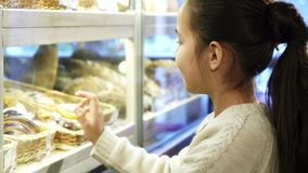 Zamyka w górę strzału ładna mała dziewczynka posinting przy deserami przy piekarnią zdjęcie wideo