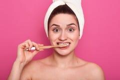 Zamyka w górę strzału dziewczyna z śmiesznym wyrazem twarzy, pozuje z toothbrush, młoda kobieta czyści jej zęby, stoi w łazience zdjęcie royalty free