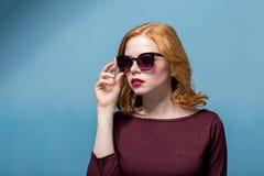 Zamyka w górę strzału elegancka młoda kobieta ono uśmiecha się przeciw błękitnemu tłu w okularach przeciwsłonecznych piękna kobie obraz stock