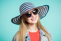Zamyka w górę strzału młoda kobieta w okularach przeciwsłonecznych i kapeluszy spojrzeń z uśmiechem przy kamerą Fotografia Stock