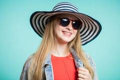 Zamyka w górę strzału młoda kobieta w okularach przeciwsłonecznych i kapeluszy spojrzeń z uśmiechem przy kamerą Zdjęcia Royalty Free