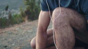 Zamyka w górę strzału młody biały męski biegacz wiąże jego buty i trwanie w górę podziwiać widok przed jego biegający zdjęcie wideo