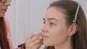 Zamyka w górę strzału Makeup artysta stosuje ciekłą tonalną podstawę na twarzy zdjęcie wideo