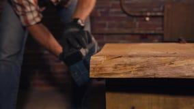 Zamyka w górę strzału pracownik który trzyma szlifierską maszynę dla woodwork zbiory wideo