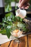 Zamyka W górę strzału ręki dolewania kawy espresso kawa Na Vanilla Ice śmietance W szkle, deser, Na Nieociosanym Drewnianym stole fotografia royalty free