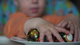 Zamyka w górę strzału ręki dziecko który wybiera Easter jajka na talerzu zbiory