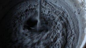 Zamyka w górę strzału wiadro cement pracownik mieszanek luźni materiały i woda, produkować cement zdjęcie wideo