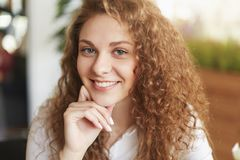 Zamyka w górę strzału zadowolona kędzierzawa urocza kobieta z szerokim uśmiechem, kędzierzawego włosy, pozuje salowego, demonstat Zdjęcie Royalty Free