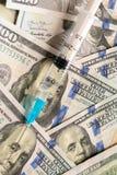 Zamyka w górę strzykawki z zastrzykiem na dolarowych banknotach obraz royalty free