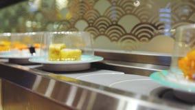 Zamyka w górę suszi i rolek na talerzach poruszających wokoło suszi baru 3840x2160 zdjęcie wideo