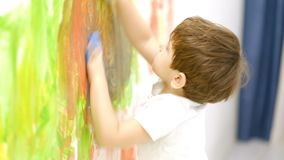 Zamyka w górę szczęśliwego małego dziecka robi kolorowemu handsprint na białej ścianie z matką wpólnie swobodny ruch zbiory