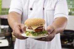 Zamyka w górę szef kuchni przedstawiającego hamburgeru obrazy stock