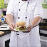 Zamyka w górę szef kuchni przedstawiającego hamburgeru obrazy royalty free