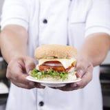 Zamyka w górę szef kuchni przedstawiającego hamburgeru zdjęcie royalty free