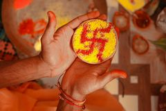 Zamyka w górę, trzyma na ręce diw brązu kolor z swastik rysującymi w nim swastyką lub i fotografia royalty free