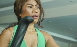 Zamyka w górę twarzy potomstwa ustalający przy gym robi treningowi w i skupiająca się Azjatycka kobieta elliptical maszynowy prze obrazy stock