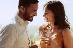 Zamyka w górę uśmiechniętej pary wpólnie trzyma win szkła obrazy stock