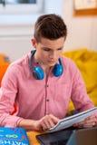 Zamyka w górę ucznia jest ubranym słuchawki na szyi robi matematyki pracie domowej fotografia royalty free