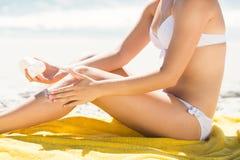Zamyka w górę widoku Ładna blondynki kobiety kładzenia suntan płukanka na jej nodze Fotografia Stock