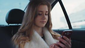 Zamyka w górę widoku atrakcyjna blondynki dziewczyna trzyma jej telefon i surfuje internet, podczas gdy siedzący w kosi samochodz zbiory