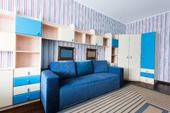 zamyka w górę widoku błękitna kanapa i drewniana szafa w żywym pokoju obrazy royalty free