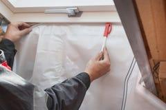 Zamyka w górę widoku dacharza budowniczego pracownik instaluje opary barierę obraz stock
