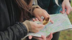 Zamyka w górę widoku dwa młodej turysta dziewczyny próbuje znajdować kierunek na mapie Przyjaciele bada dziką naturę zbiory