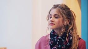 Zamyka w górę widoku elegancka młoda dziewczyna podrzuca magazyn, then stawia dalej hełmofony i cieszy się muzykę być szczęśliwym zbiory