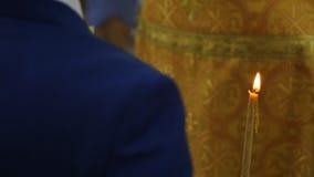 Zamyka w górę widoku mężczyzna pozycja z świeczką w kościół zdjęcie wideo