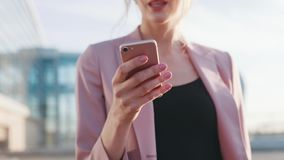 Zamyka w górę widoku malutka żeńska ręka używać telefon komórkowego dla texting Na zewnątrz strzelaniny, pogodna pogoda Elegancki zbiory