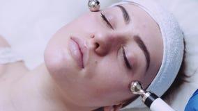 Zamyka w górę widoku piękna żeńska twarz masuje z narzędzia kosmetologii masażu narzędziem Skóry opieka, ciało opieka zbiory wideo