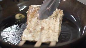 Zamyka w górę widoku ziele, czosnek i oliwa z oliwek na smaży niecce, szef kuchni dodaje ziobro Kucbarskiego narządzania mięsny j zbiory