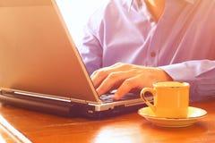 Zamyka w górę wizerunku mężczyzna używa laptop obok filiżanki kawy prętowej wizerunku damy retro dymienia styl Selekcyjna ostrość Obrazy Stock
