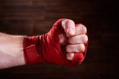 Zamyka w górę wizerunku pięść bokser z czerwonym bandażem przeciw brown tłu obraz stock