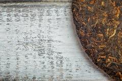 Zamyka w górę wizerunku Shu puerh stary chińczyk fermentującej herbaty na nieociosanym drewnianym tle Obrazy Royalty Free